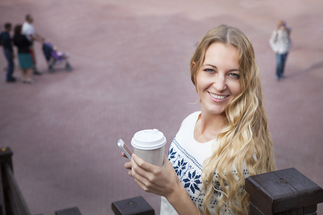 Smiling fashionable blonde woman holding coffee outdoors on street background